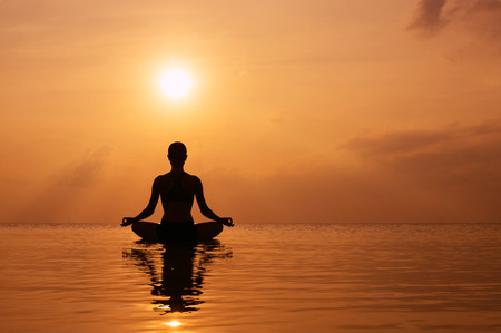 Silhouette young woman practicing yoga on the beach at sunset Banque d'images