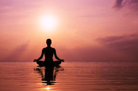 Silhouette jeune femme pratiquant le yoga sur la plage au coucher du soleil Banque d'images - 34786928