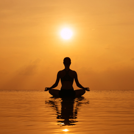 Silhouette young woman practicing yoga on the beach at sunset Stockfoto