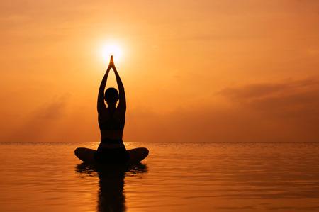Silhouette jeune femme pratiquant le yoga sur la plage au coucher du soleil Banque d'images - 34786933