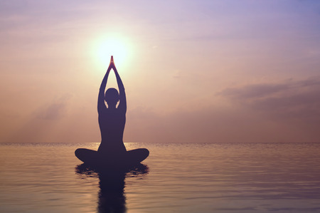Silhouette young woman practicing yoga on the beach at sunset Stock Photo
