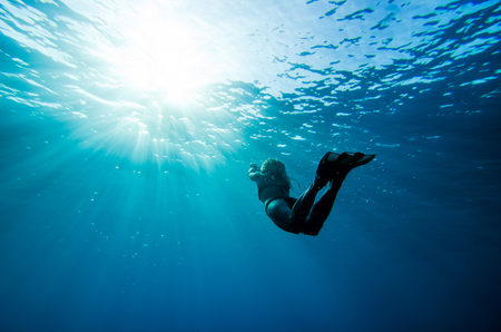girl swimming underwater in deep blue tropical sea photo