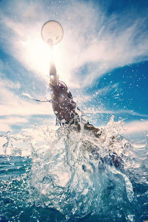 weekend activities: young man jumping in the water, summer beach activity