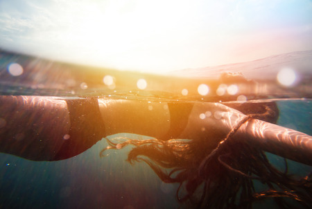 Girl underwater with sun rays and colorful sunflare