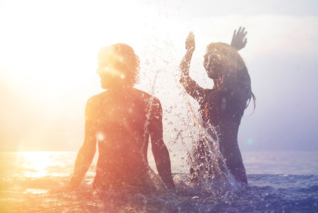 happy young couple having fun, man and woman in the sea on the beach, summer