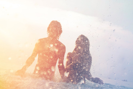 gelukkig jong paar dat pret, man en vrouw in de zee op het strand, in de zomer