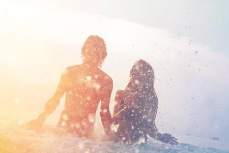lyckligt ungt par att ha roligt, man och kvinna i havet på stranden, sommar