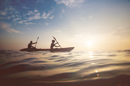 adventure holiday: silhouette of a couple on a boat in the sea at sunset