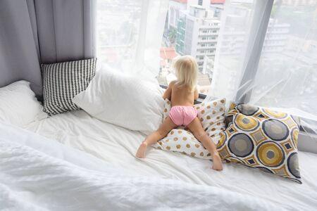 kind kijkt uit het raam in de grote stad