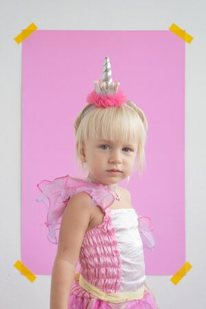 girl in a unicorn costume on a pink background