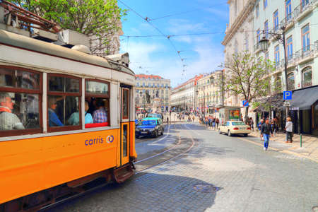 LISBON, PORTUGAL-OCTOBER 2017: Tourists sightseeing Lisbon on a famous yellow tram Редакционное