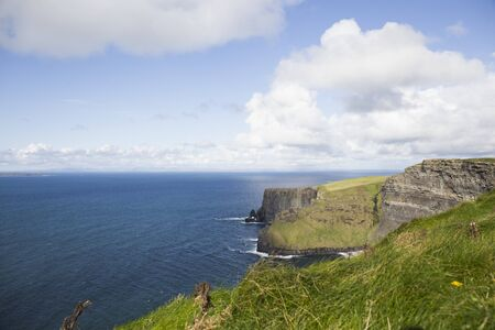 landscape of moher cliffs in ireland, green vegetation, blue sea and cloudy sky