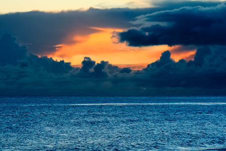 Abright orange sunset coming out from a stormy sky on a blue choppy ocean