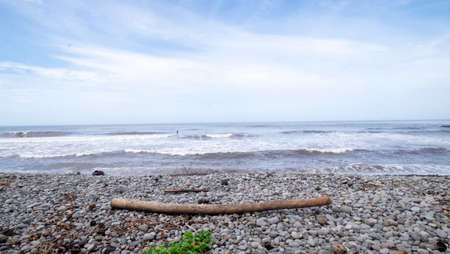 El Tunco stone beach and driftwood during sunny day, El Salvador