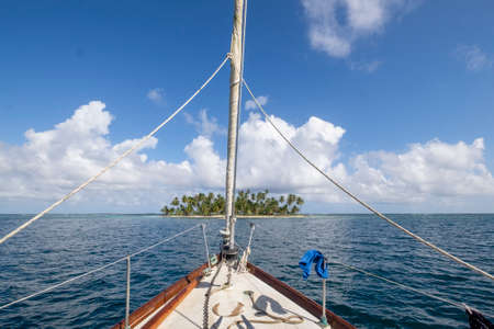 Sailboat prow pointed to a paradise tropical island with palm trees on the San Blas archipelago