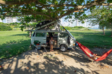 Cartagena, Colombia - November, 30th, 2018: couple camping with westfalia van and city background 新聞圖片