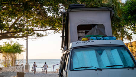 Rodadero, Colombia - December 13rd, 2018: two man walking towards the beach and a westfalia camper van