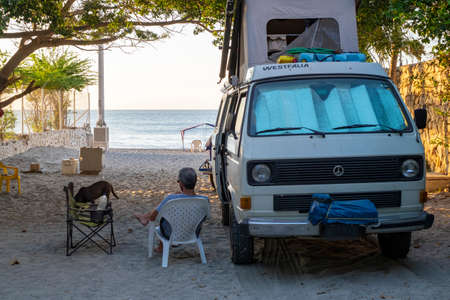 Rodadero, Colombia - December 13rd, 2018: Man sit outside a westfalia camper van looking out at the beach 新聞圖片
