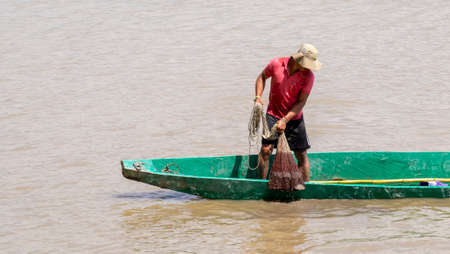 Magdalena river, Cambao, Colombia, January, 27th, 2019: artisan fisherman at daily task with a casting net