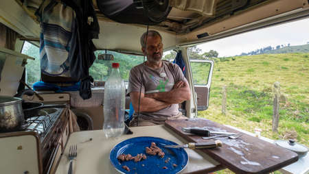 Murillo, Colombia January, 28th, 2019: daily scene of meal inside a westfalia camper van with man