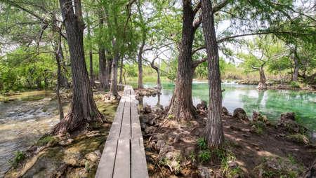 Wooden walk board leading to green natural pool at Lagos de Colon recreation area, Chiapas, Mexico, Stock Photo