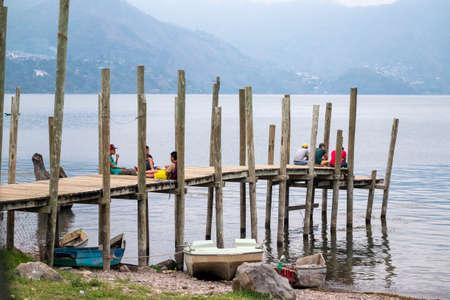 San Pedro La Laguna, Guatemala - May, 23rd, 2018: local kids sit on the wooden pier