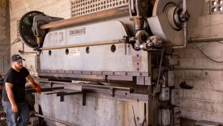 La Paz, Mexico - December, 15th ,2017: Old mechanical press brake industrial equipment maneuver by workers
