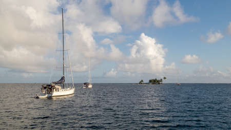 San Blas Archipelago, Panama - November 22nd, 2018: Sailing boats on the sea with and palm tree islands on the horizon