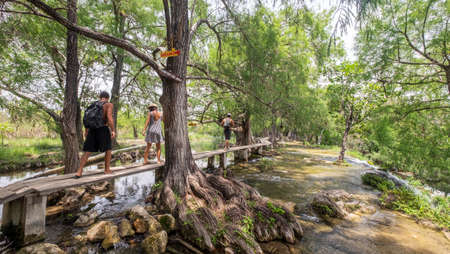 Lagos de Colon, Chiapas, Mexico - may 21st, 2018: tourists walking on wooden walk board over the river