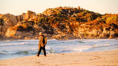Pochutla, Oaxaca, Mexico - January, 27th, 2018: man walking on the beach at golden hour, Mojon beach