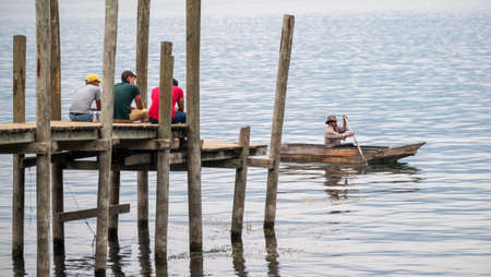 San Pedro La Laguna, Guatemala - May, 23rd, 2018: local kids sit on the wooden pier and canoe with fisherman Editorial