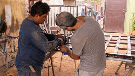 La Paz, Baja California, Mexico - December, 13th, 2017: blacksmith working in a backyard workshop Editorial