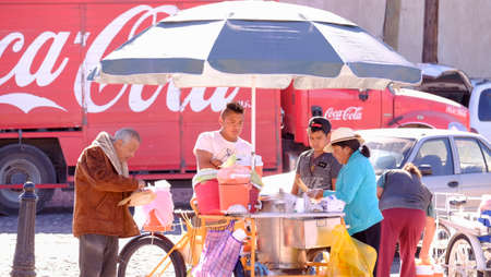 Aculco, Mexico, January, 9th, 2018: Street food vendor stall with people around on a sunny beautiful day