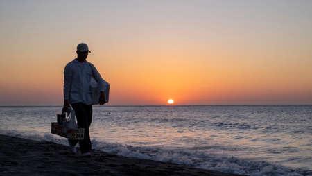 Rodadero, Colombia - December 13rd, 2018: seller walking along the beach at sunset