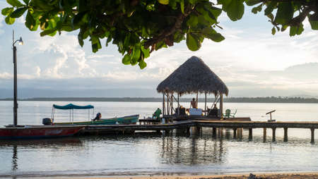 Bocas del Toro, Panama - September 11th, 2018: pier construction with tiki gazebo at the end during sunset at Boca del Drago beach Editorial