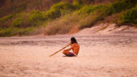 Mazunte, Oaxaca, Mexico - January, 24th, 2018: man on the beach playing didgeridoo at Mermejita beach Editorial