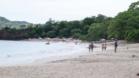 Conchal Beach, Costa Rica - July 4th, 2018: Crystal blue waters on Conchal beach in the pacific coast of Costa Rica with people walking along the long beach