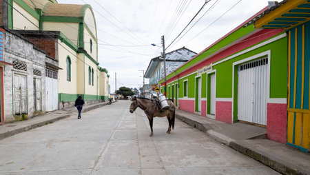 Murillo, Colombia -January, 29th, 2019: street with painted facades houses and a donkey with milk production Editorial