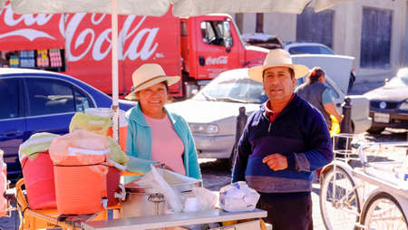 Aculco, Mexico - January, 9th, 2018: Street food vendor stall with couple smiling at the camera