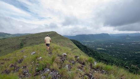 Male hiker walking along the ridge on top of India Dormida mountain in El Valle de Aton, Panama Stock Photo