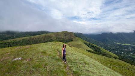 Female hiker walking along the ridge on top of India Dormida mountain in El Valle de Aton, Panama