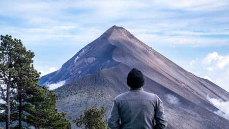 Fire volcano in Guatemala with hiker overlooking the peak