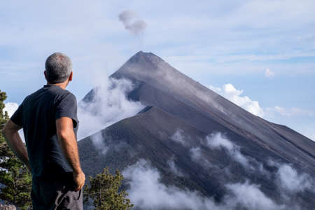 Fire volcano in Guatemala with hiker looking the eruption
