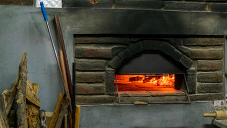 Wooden oven full of logs on fire and ready to make pizza