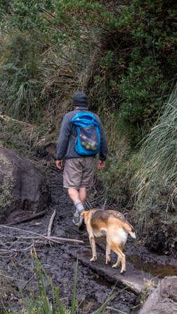 Man and dog hiking on muddy terrain