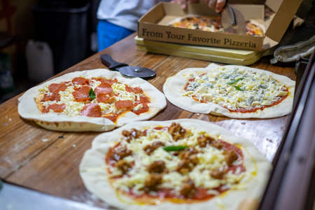Detail of Three different pizzas on display and one in a box for take away Stock Photo