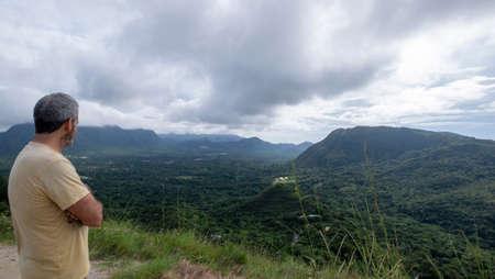Hiker at the top of India Dormida Mountain overlooking the town of El Valle de Anton, Panama