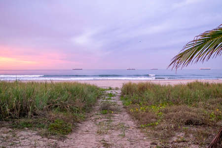 A trail heading to an empty beach at sunset and cargo ship on the horizon, Mazatlan, Mexico