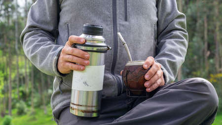 Hands holding thermo and calabash gourd for yerba mate