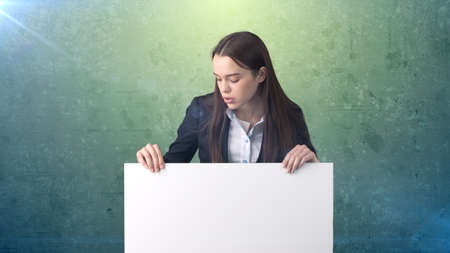 one sheet: Serious Business woman portrait with blank white board on green isolated . Female model with long hair.